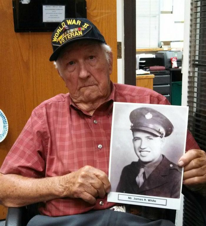Man wearing World War II hat holds black and white image of James White